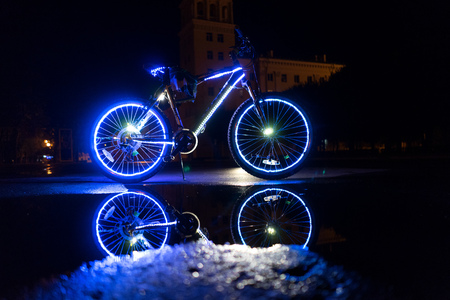 Glowing bicycle is reflected in the water.