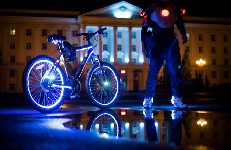 Glowing bicycle is reflected in the water. Nearby is a man in luminous shoes-2