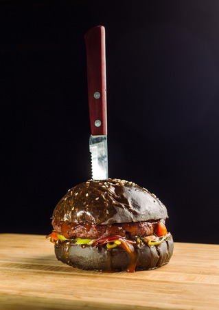 Close-up of delicious fresh home made burger with lettuce, cheese, onion and tomato. Black bun.