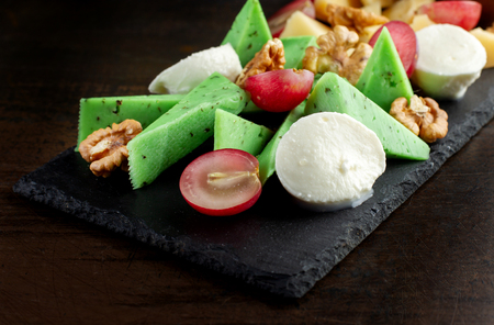 Cheese plate on black shale. Pieces of fruit. Stock Photo