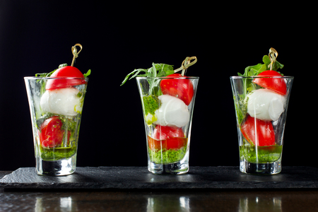 Canapes of tomatoes and cheese in a glass. Three cups.