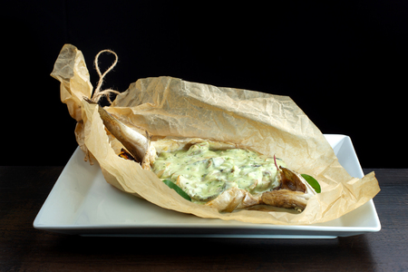 Stuffed fish wrapped in kraft paper. On white plate.