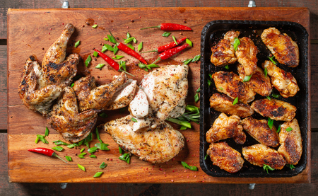 Grilled chicken wings laid out in a cast-iron tray. Tasty, beautiful and appetizing.