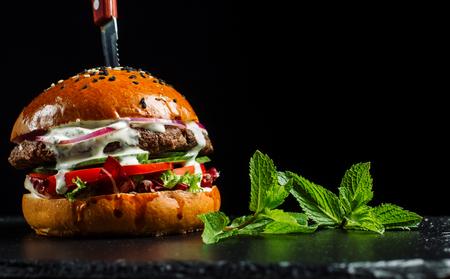 Delicious fresh homemade burger on black slate.