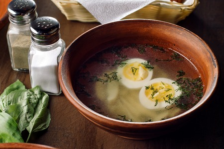 Chicken soup with egg and dill in the clay plate. Фото со стока