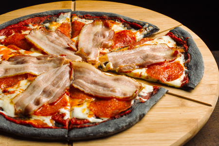 Pepperoni pizza with ham and sausages on black pastry. Stock Photo