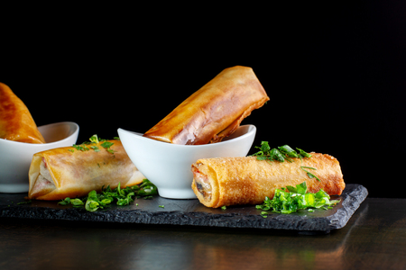 Involtini primavera fritti su ardesia nera decorata con verdure. Archivio Fotografico