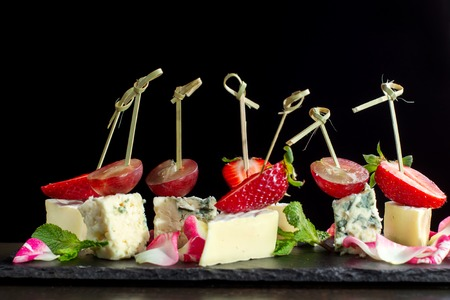 Cheese plates served with strawberry and grapes on black slate.