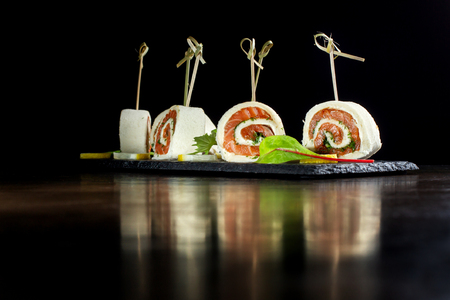 Rolls with salmon and dill laid out on a black slate.