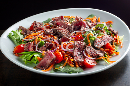Beef salad sprinkled with sesame and garnished with onion rings.