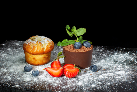Vanilla cap cake and chocolate dessert in a pot on a black slate covered with powdered sugar. Standard-Bild