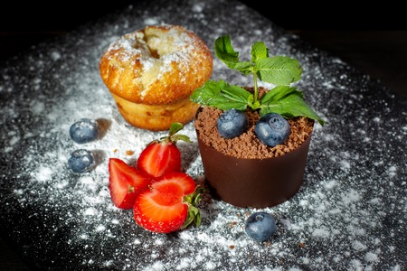Vanilla cap cake and chocolate dessert in a pot on a black slate covered with powdered sugar. Фото со стока