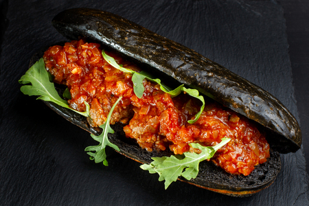 Black hot dog bun with minced meat. Stock Photo