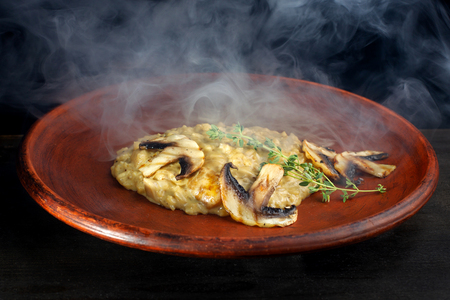 Wheat porridge with mushrooms on a black background in a clay plate.