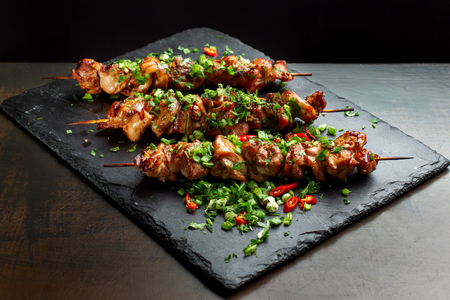 Grilled meat skewers, shish kebab on black slate-2. Imagens