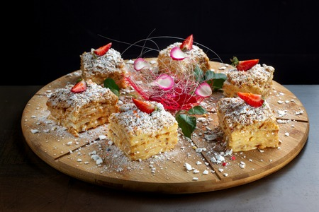 Six piece of cake Napoleon on wooden tray. Russian cuisine, layered cake with pastry cream.