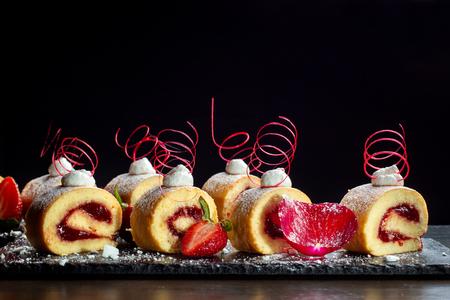 Homemade cake roll with strawberry cream a on a black slate. Stok Fotoğraf