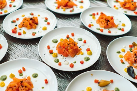 Plates with sliced salmon, designer decorated cook. Imagens