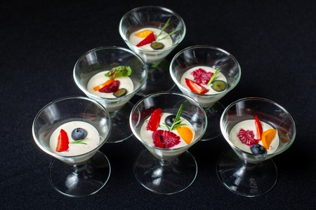 Creamy dessert with summer berries in a glass ice-cream bowl.