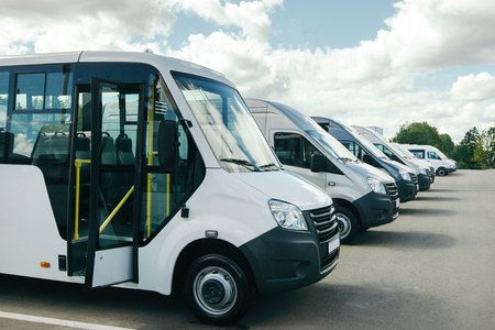 Number of new white minibuses and vans outside. Beautiful white clouds. Stock Photo