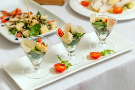 Salad in cups, with tomatoes, sauce and greens. Diagonal composition.
