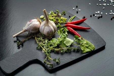 Garlic, onion and pepper on the black slate. Archivio Fotografico