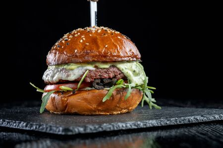 Burger with olives, tomatoes, herbs and pesto.