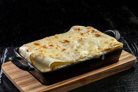 Piece of tasty hot lasagna. Traditional italian lasagna on a cast iron pan.