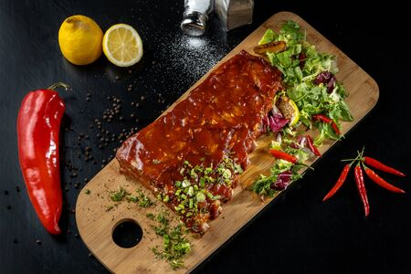 Pork ribs with sauce laid out on a wooden board.
