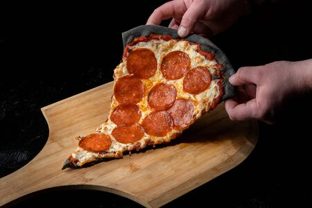 A slice of pepperoni pizza, on black dough. Lies on a wooden platform.