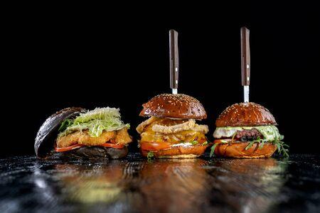Trois hamburgers avec viande, rondelles d'oignon, galette de boeuf et nuggets de poulet. Banque d'images