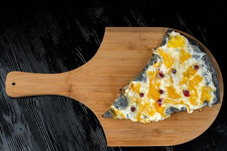 A slice of pizza with cranberries from black dough lying on a wooden board. Imagens