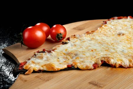 A slice of pizza from black dough lying on a wooden board. Imagens