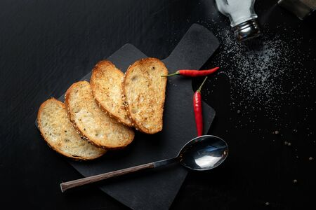 Toast the bread on a black slate, next is red pepper.