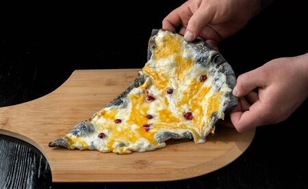 A slice of pizza with cranberries from black dough lying on a wooden board. A man raises a slice of pizza with his hands.