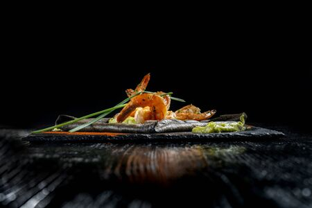 Pancakes made of black dough, with shrimp and sauces. Laid out on black slate. Stock Photo