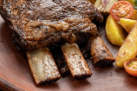Ethically raised, fresh cut organic rib eye steak grilled with fried potatoes. Banque d'images