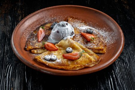 Pancakes with ice cream, with blueberries and strawberries, sprinkled with icing sugar. Stock fotó