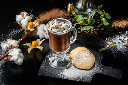 Chocolate dessert, hot chocolate with ice cream pieces, around a beautifully decorated table.