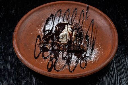 Chocolate brownie with vanilla ice-cream and chocolate sauce is laid out on a clay plate. Stock fotó