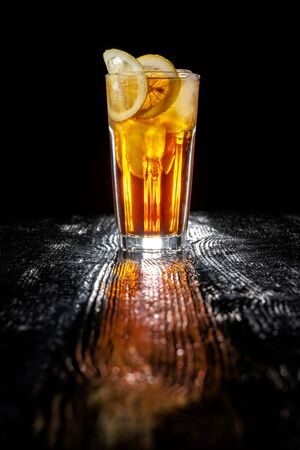 Long island ice tea. Standing on a varnished black table. 스톡 콘텐츠