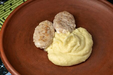 Cutlets with mashed potatoes, laid out on a clay plate.