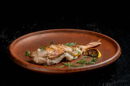 Grilled sea bass on a beautiful clay plate. Sprinkled with dill and garnished with lemon. Side view.