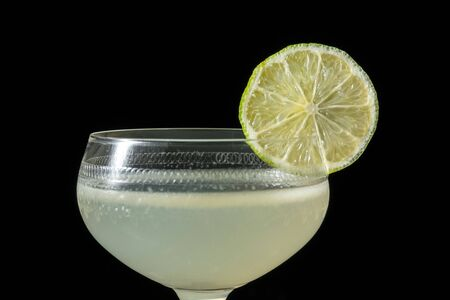 Classic daiquiri on the dark background. Luxury craft drink. Decorated with a slice of lime in a glass on a thin leg. Stok Fotoğraf