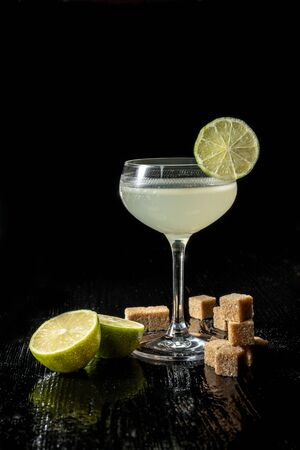 Classic daiquiri on the dark background. Luxury craft drink. Decorated with a slice of lime in a glass on a thin leg. Next to the table lies a whole lime and cubes of brown sugar.