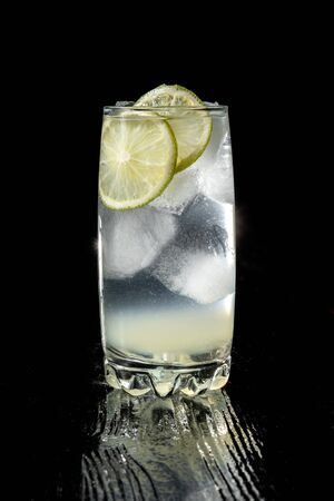 Vodka lime, gimlet or gin tonic with ice in rocks glass on black background. Beautiful back light.