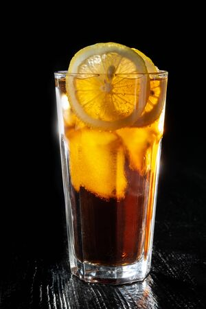 Long island ice tea. Standing on a varnished black table, beautiful backlight.