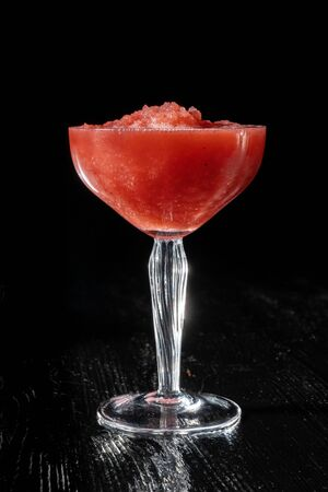 Strawberry daiquiri cocktail with strawberry syrop, on black background. Summer drink, refreshment, Aperitif. Side view.