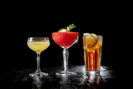 Three cocktails, Strawberry daiquiri, Long island and daiquiri on black background. Imagens