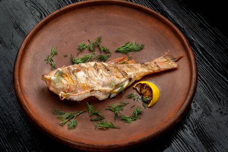 Grilled sea bass on a beautiful clay plate. Imagens